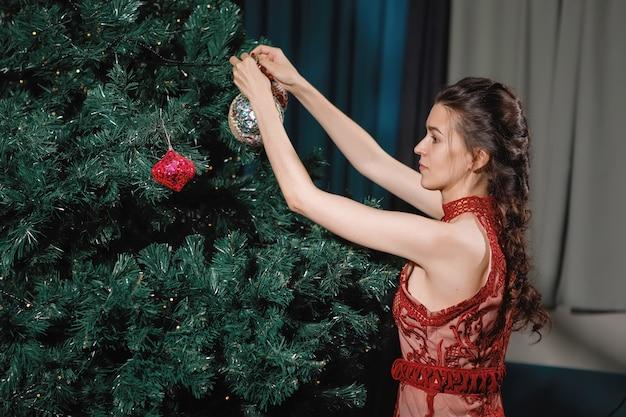 おさげの女性は家の内部のクリスマスツリーを飾ります。