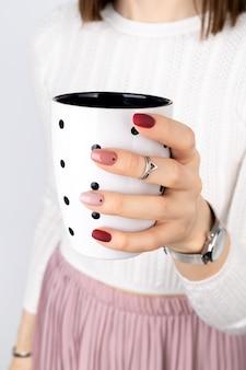 커피 또는 차 한 잔을 들고 최소한의 스타일에 분홍색 매니큐어를 가진 여자. 여름 봄 네일 디자인. 패션 액세서리 실버 주얼리 제품 컨셉