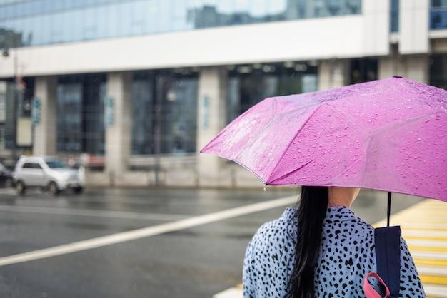 都市の背景に雨の天候でピンクの傘を持つ女性。雨の日。シティストリートスタイル。