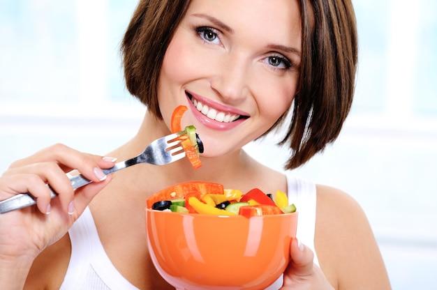 Женщина с тарелкой овощного салата в руках
