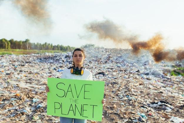 ポスターを持った女性が地球を救い、ゴミで汚染された環境をピケットし、燃える火と黒い煙