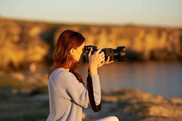 山の屋外でプロのカメラを持つ女性は、海の近くの夕日を撮影します