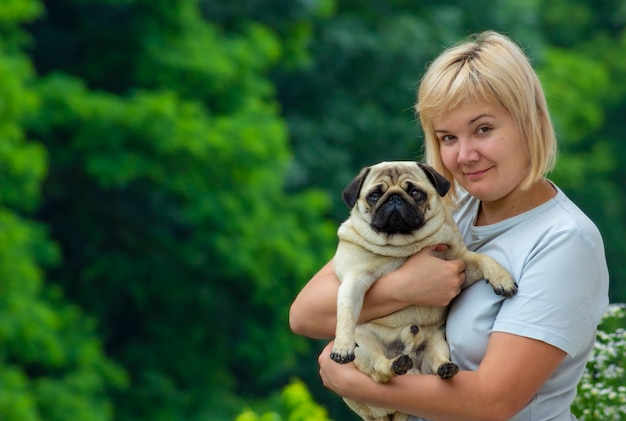 彼女の腕にパグ犬を持つ女性。