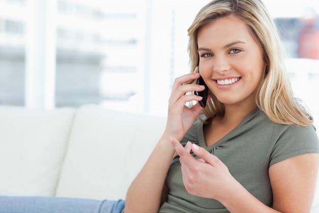 女は、手を挙げて、電話をかけて、笑顔で前向きに