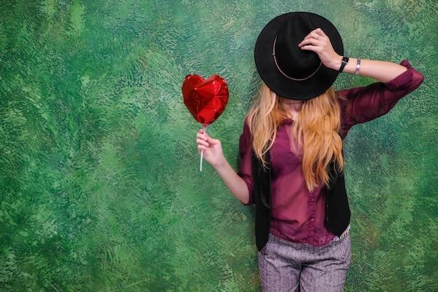 Женщина с красным сердцем из воздушного шара в день святого валентина 14 февраля.
