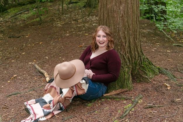 葉と枝で覆われた森の木に寄りかかってスカーフと帽子を持つ女性
