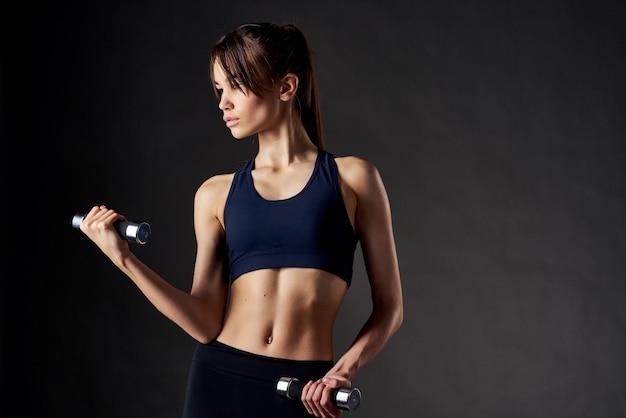 スリムな体型の膨らんだ筋肉を持つ女性は、フィットネスのクローズアップを行使します