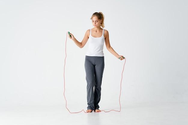 スリムな体型の女性は縄跳び運動ジムで運動します。高品質の写真