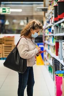 スーパーマーケットでマスクを着用しながら購入する商品を選ぶスマートフォンを持つ女性