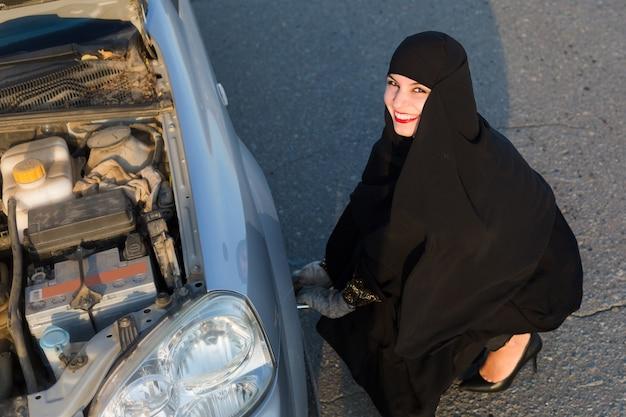 Женщина с улыбкой меняет проколотое колесо на машине