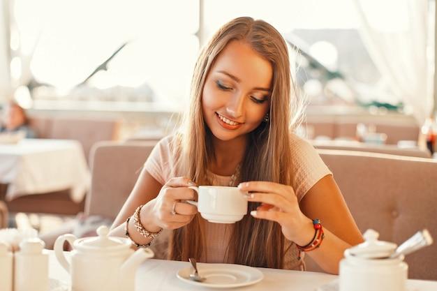レストランでお茶を飲む笑顔の女性。