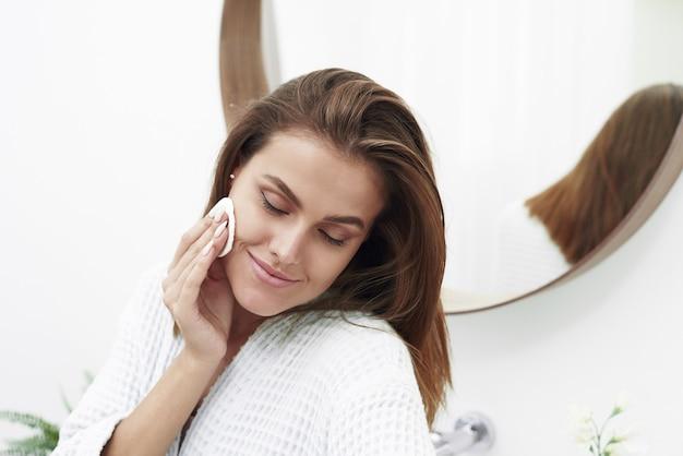 스폰지면 패드 문제 피부를 가진 여자입니다. 욕실에 목화 패드로 그녀의 얼굴을 청소하는 행복한 여자의 그림. 깨끗하고 신선한 피부를 가진 젊은 여자의 아름 다운 얼굴.