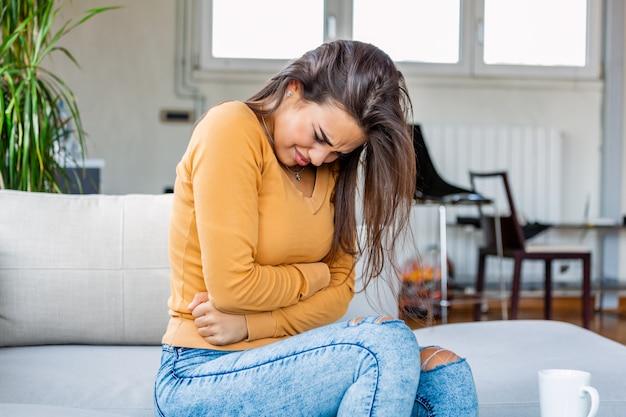 ソファーに座っていた胃の痛みを持つ女性