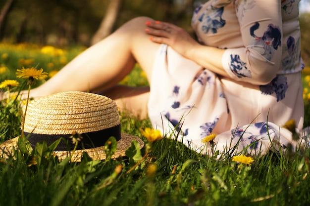 花畑と緑の草の麦わら帽子を持つ女性。田舎の夏。帽子に焦点を当てる