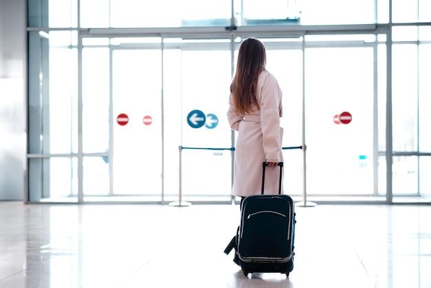 スーツケースを持った女性が駅を出ます。