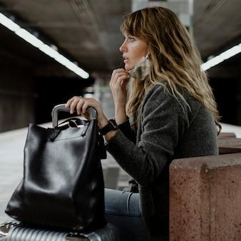 코로나 바이러스 전염병 동안 기차를 기다리는 여행 가방을 가진 여성
