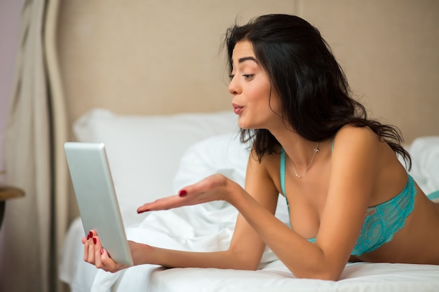 Женщина с планшетом лежа.