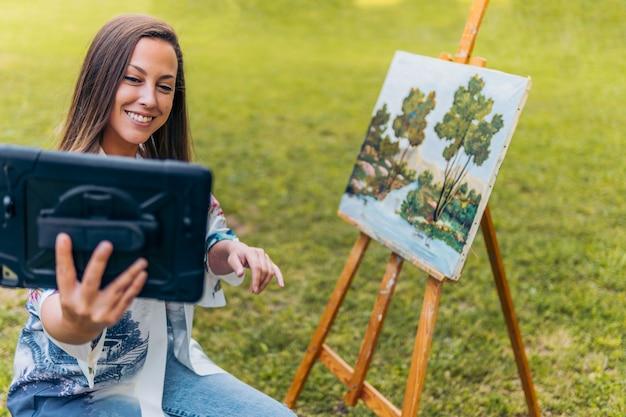Женщина с планшетом делает видеозвонок, чтобы показать свою краску в парке