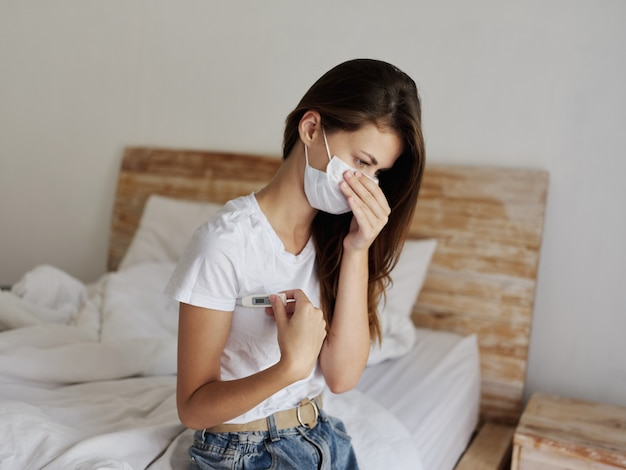 Женщина с термометром под мышкой в медицинской маске сидит на кровати