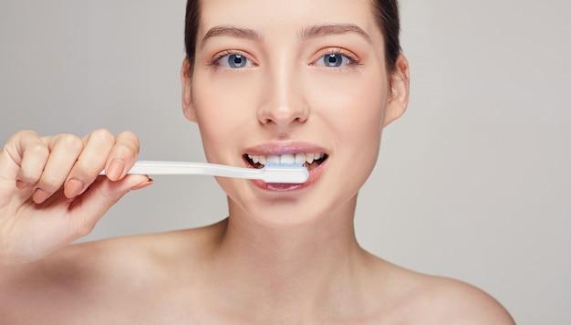 Женщина с зубной щеткой в руках у рта с белыми зубами