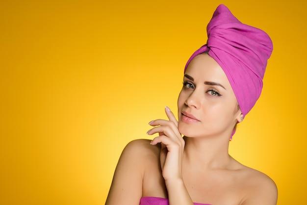 노란색 배경에 샤워 후 머리에 수건을 두른 여자