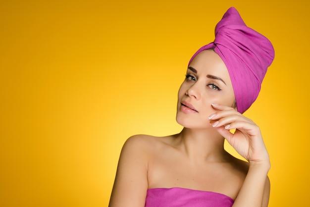 샤워 후 머리에 수건을 두른 여성이 노란색 배경의 카메라에 포즈를 취하고 있다