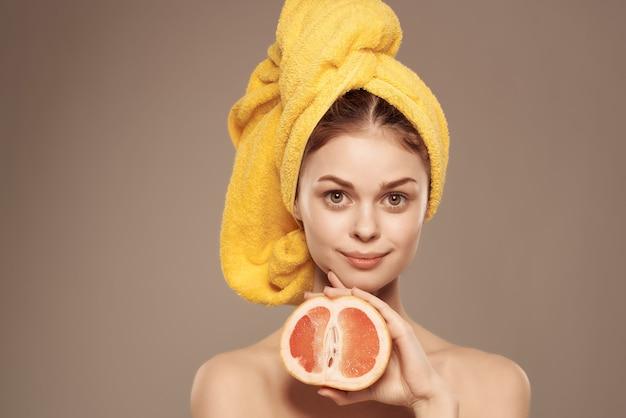 샤워 비타민 포즈를 취한 후 머리에 수건을 두른 여자
