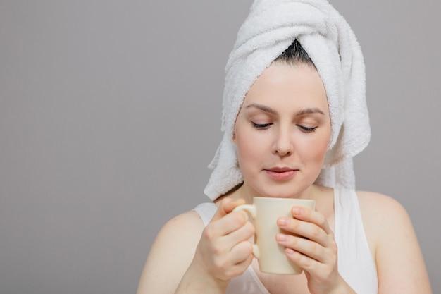 그녀의 머리와 컵에 수건을 가진 여자