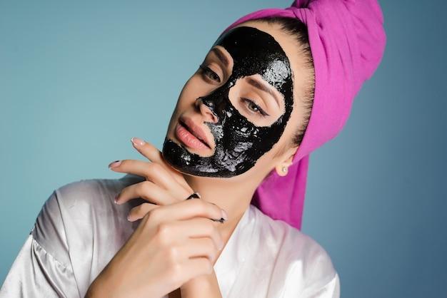 頭にタオルをかぶった女性がマスクをして顔の皮膚をきれいにした