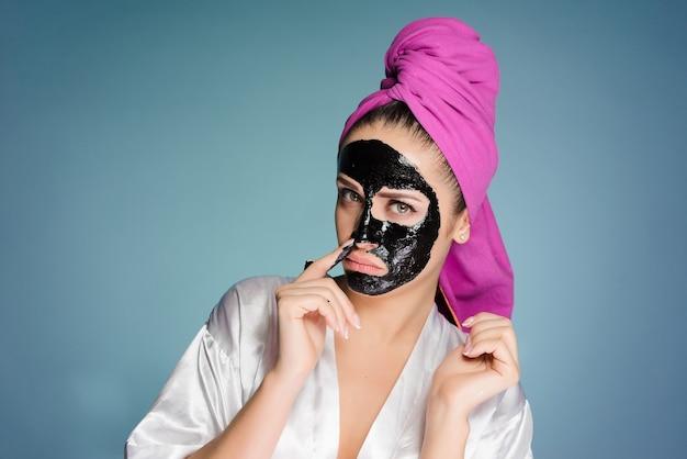 頭にタオルをかぶった女性が顔の皮膚にマスクをかけた