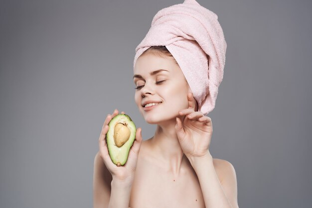그녀의 머리에 수건을 가진 여자 깨끗한 피부 아보카도 포즈 근접 촬영