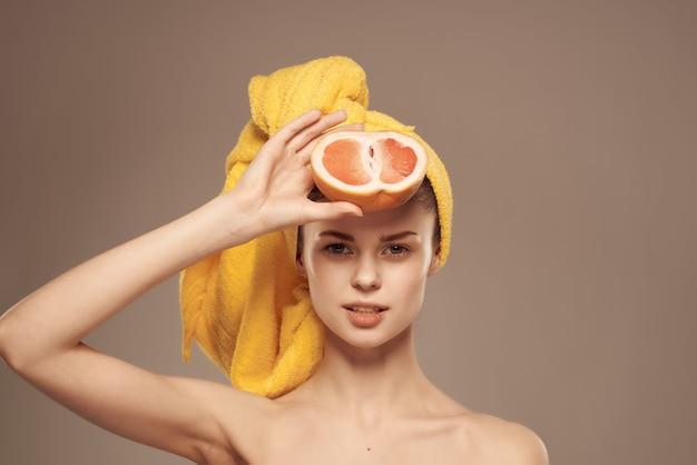 그녀의 머리에 수건을 가진 여자 손 자른 보기에 깨끗한 피부 자몽