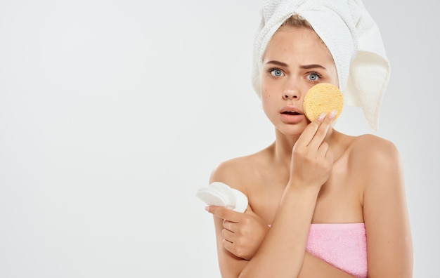 그녀의 머리에 수건을 가진 여자는 그녀의 손 미용 피부과 모델에 스폰지를 보유하고 있습니다.