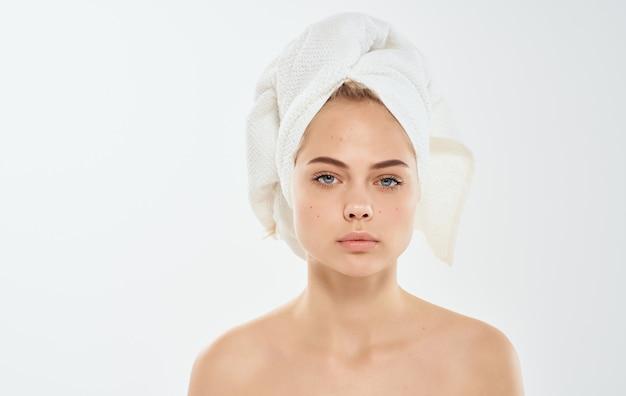 그녀의 머리에 수건을 가진 여자 벌거 벗은 어깨 우리가 피부로 직면하는 젖은 머리카락 문제.