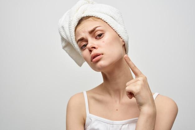 明るい背景に頭にタオルを、顔ににきびを持った女性。移行期のきれいな肌のモデル。高品質の写真