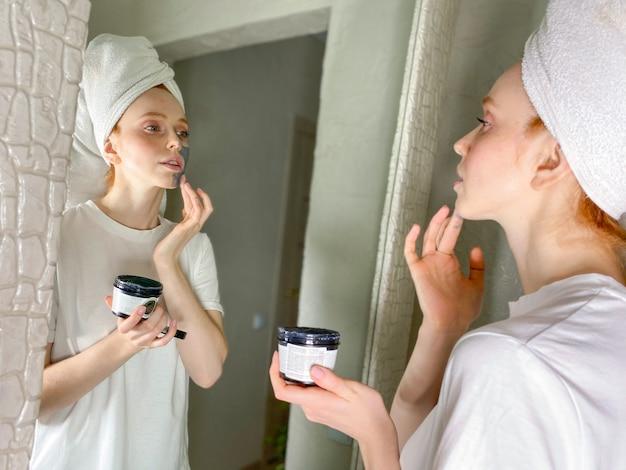 Женщина с полотенцем на голове кладет на лицо глиняную маску дома