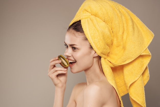 手でトリミングされたビューで彼女の頭のスキンケアキウイにタオルを持っている女性