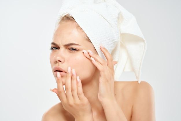 Женщина с полотенцем на голове проблемы кожи лица светлый фон