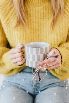 彼女の眼鏡を保持している暖かいお茶のカップを持つ女性