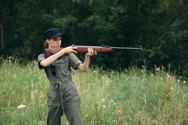 Женщина с оружием в руках в охотничьем зеленом комбинезоне нацелена на свежий воздух крупным планом
