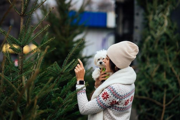 시장에서 녹색 크리스마스 트리 근처 그녀의 팔에 흰 개를 가진 여자