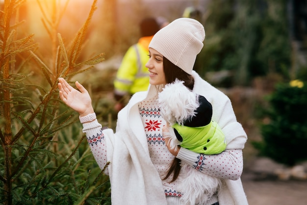 市場で緑のクリスマスツリーの近くで彼女の腕に白い犬を持つ女性