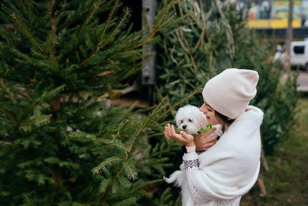 시장에서 녹색 크리스마스 트리 근처에 그녀의 팔에 흰색 개를 가진 여자