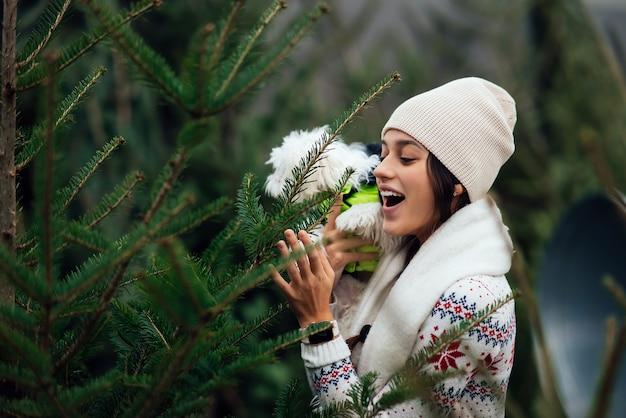 녹색 소나무 근처에 그녀의 팔에 흰 개를 가진 여자 프리미엄 사진
