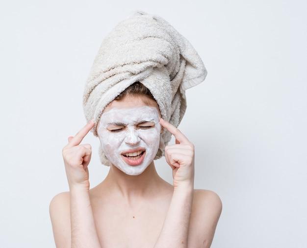 Женщина с белой маской против черных точек на лице и полотенцем на голове.