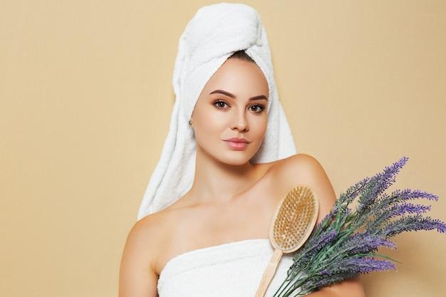 Женщина с белым полотенцем на голове и кистью для кожи в руках