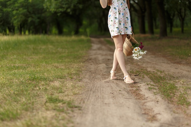 Женщина с плетеной корзиной и цветами на проселочной дороге.