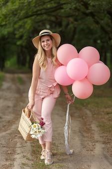 Женщина с плетеной корзиной, шляпой, розовыми баллонами и цветами, идущими по проселочной дороге.