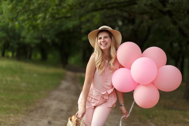 Женщина с плетеной корзиной, шляпой, розовыми баллонами и цветами гуляет по проселочной дороге
