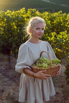 Женщина с плетеной корзиной зеленого винограда